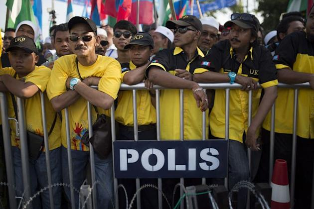 Supporters wait behind a police fence as Malaysia's opposition leader Anwar Ibrahim (unseen) submits his election nomination in Berapit on April 20, 2013. Hundreds of cases of Malaysian election violence have been reported since campaigning for tightly contested May 5 polls got under way at the weekend, police were quoted saying on Wednesday