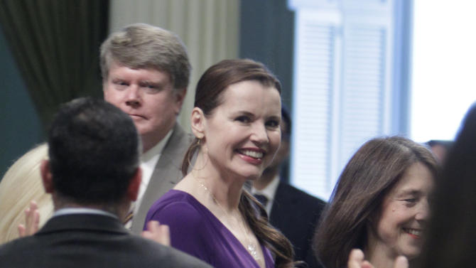 Actress Geena Davis receives a standing ovation from members of the state Assembly as she is escorted down the center aisle by Assemblywoman Nancy Skinner, D-Berkeley, right, at the Capitol in Sacramento, Calif., Monday, March 4, 2013. Davis, who is the chairwoman of the Commission on the Status of Women, was one of several women honored for their accomplishments.(AP Photo/Rich Pedroncelli)