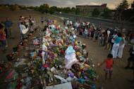 People are seen visiting a memorial setup across the street from the Century 16 movie theatre where James Holmes is suspected of a mass shooting, on July 26, in Aurora, Colorado