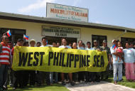 Unidentified Philippine lawmakers join local residents and military officials in a symbolic unfurling of a banner at Pagasa Island, part of the disputed Spratly group of islands, in the South China Sea located off the coast of western Philippines Wednesday, July 20, 2011. China protested a trip made by Filipino lawmakers, who are pushing to use the term 'West Philippine Sea' instead of South China Sea, to disputed areas in the South China Sea to assert the claim of the Philippines. Ethan Sun, spokesman for the Chinese embassy in Manila, said the trip scheduled was 'against the spirit' of a code of conduct signed by claimants to the areas in 2002. The Spratlys, believed to be rich in oil, mineral and marine resources, are also claimed in whole or partly by Brunei, Malaysia, Vietnam and Taiwan. (AP Photo/Rolex Dela Pena, Pool)