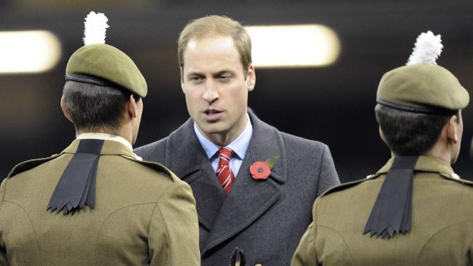 Britain's Prince William holds a South African rugby union soft toy as he talks to soldiers after the international rugby union match between South Africa and Wales at the Millennium Stadium in Cardiff,