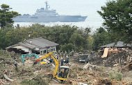 Soldiers remove debris from a houses damaged by a landslide at Oshima island, Japan on October 19, 2013