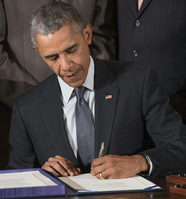 US President Barack Obama signs a bill which includes fast track trade authority that allows him to negotiate trade treaties, including the Trans-Pacific Partnership, in Washington, DC, June 29, 2015