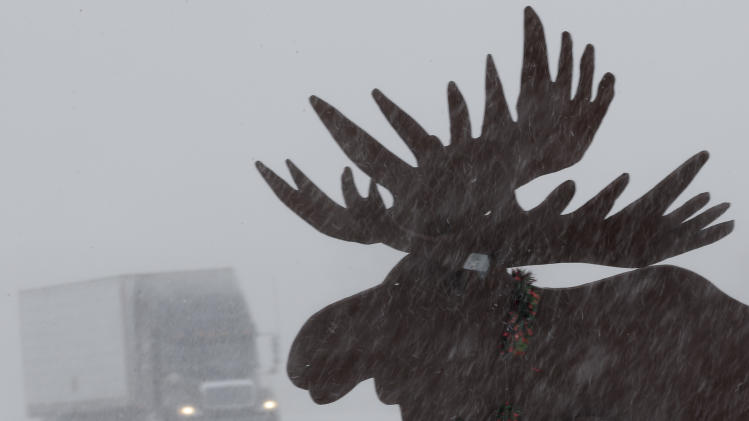A truck drives in near whiteout conditions past a silhouette of a moose, on Interstate 80 near Gretna, Neb., Thursday, Feb. 21, 2013. Much of the nation's heartland is experiencing heavy snow, treacherous roads as potentially dangerous winter storm pushed eastward out of the Rockies. (AP Photo/Nati Harnik)