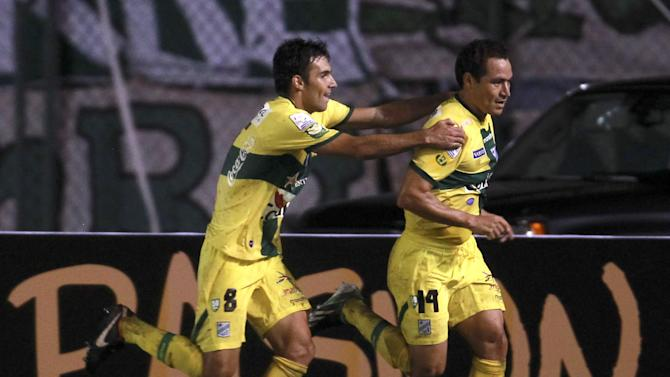 Danny Bejarano of Bolivia's Oriente Petrolero, left, reaches out to congratulate his teammate Gualberto Mujica, who runs in celebration after scoring against Uruguay's Nacional during a Copa Libertadores soccer match in Santa Cruz, Bolivia, Tuesday, Jan. 28, 2014. Oriente Petrolero won 1-0