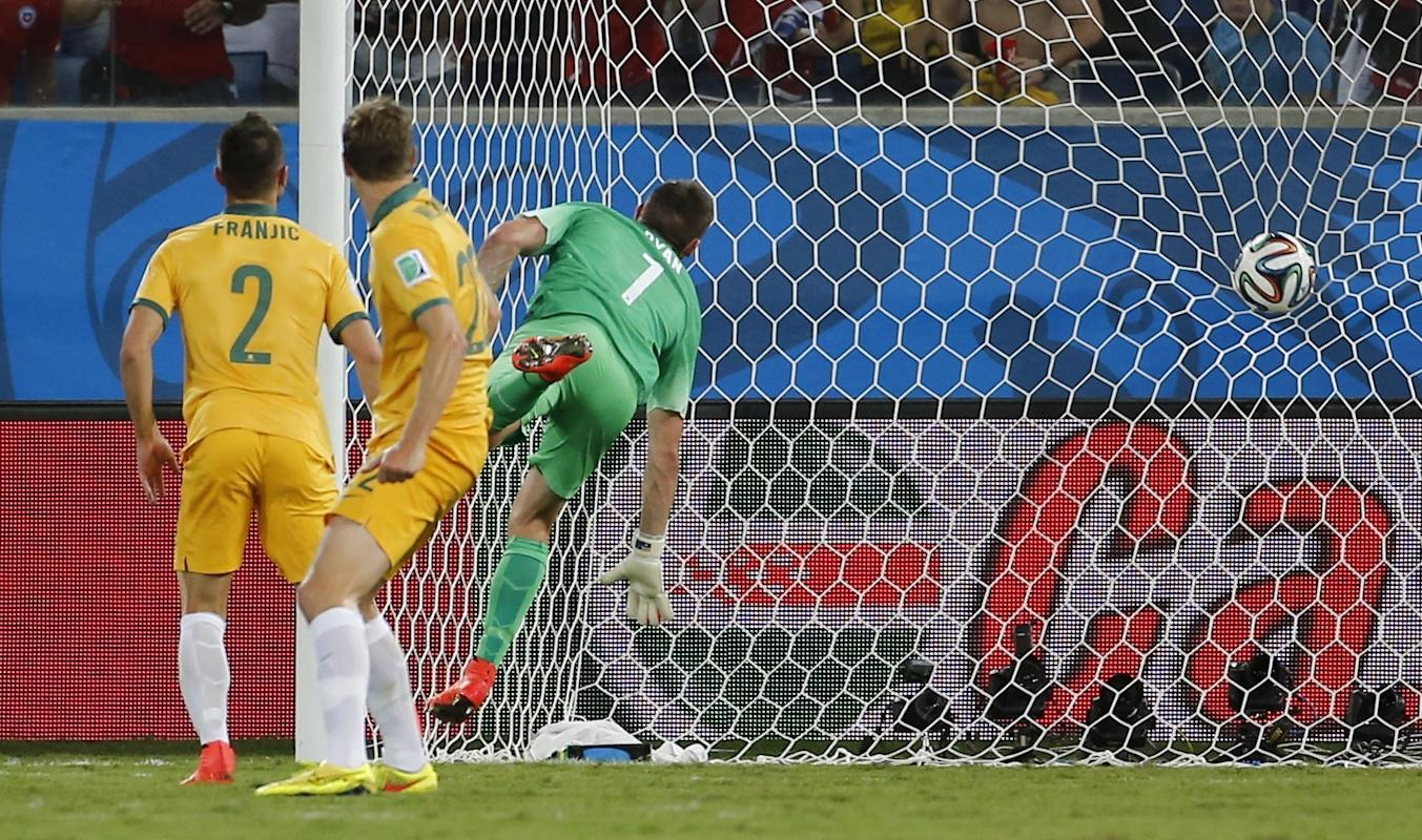 Australia's Mathew Ryan looks at the ball hit the net as Chile's Jorge Valdivia scores a goal during their 2014 World Cup Group B soccer match...