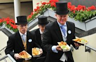 Racegoers with fish and chips at Ascot race course, west of London. The provenance of the humble fried potato, or chip for the English, is a matter of dispute among experts