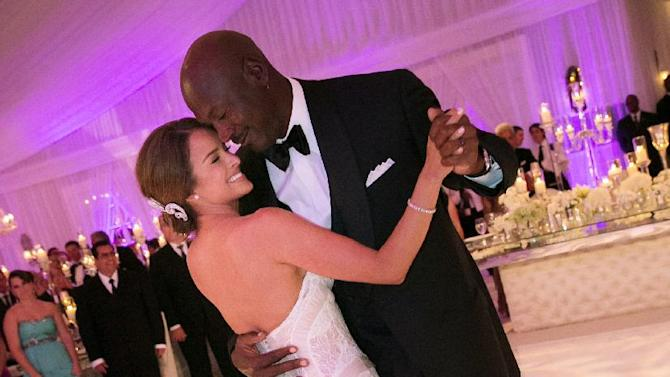 In this Saturday, April 27, 2013, photo provided by JUMP.DC, Charlotte Bobcats owner Michael Jordan dances with his bride Yvette Prieto during their wedding reception at the Bear's Club in Jupiter, Fla. The wedding took place at the Episcopal Church of Bethesda-by-the-Sea with more than 300 guests in attendance, including Tiger Woods, Patrick Ewing and Ahmad Rashad, Jordan's manager Estee Portnoy told The Associated Press Sunday. (AP Photo/JUMP.DC, Joe Buissink)  MANDATORY CREDIT