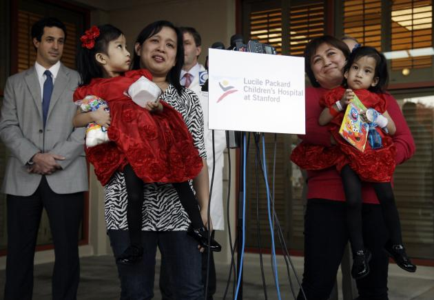 Angelina Sabuco, at left, is held by her mother Ginady Sabuco and twin sister Angelica, is held by aunt Marita Sabuco, at Lucile Packard Children's Hospital, Monday, Nov. 14, 2011 in Stanford, Calif.