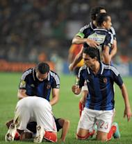 Egypt's Al-Ahly players pray after teammate, forward Nagi Ismail (bottom L), scores a goal against Esperance de Tunis during their CAF Confederation Cup match at Rades Olympic stadium near Tunis, on November 17, 2012. Ahly this year extended a record haul of CAF Champions League titles to seven