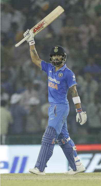 India's Virat Kohli raises his bat after scoring 150 runs during the third one-day international cricket match against New Zealand in Mohali, India, Sunday, Oct. 23, 2016. (AP Photo/Tsering Topgya
