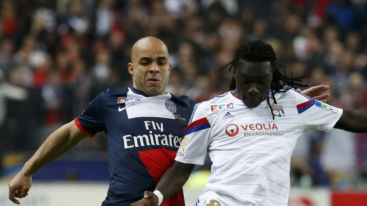 Paris St Germain's Alex challenges Olympique Lyon's Gomis during their French League Cup final soccer match at the Stade de France stadium in Saint-Denis