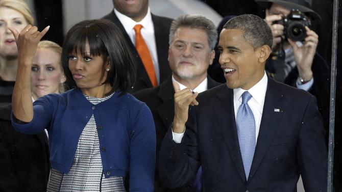 President Barack Obama and first lady Michelle Obama greet the Hawaii Home State Float during the inaugural parade Monday, Jan. 21, 2013, in Washington. Thousands  marched during the 57th Presidential Inauguration parade after the ceremonial swearing-in of President Barack Obama. (AP Photo/Gerald Herbert)