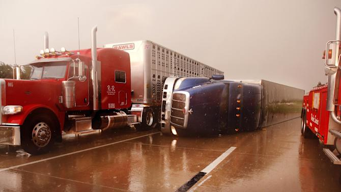 A truck squeezes past an overturned tractor-trailer on I-40 west of Banner Rd. Friday, May 31, 2013 in El Reno, Okla. (AP Photo/The Oklahoman, Jim Beckel) LOCAL STATIONS OUT (KFOR, KOCO, KWTV, KOKH, KAUT OUT); LOCAL WEBSITES OUT; LOCAL PRINT OUT (EDMOND SUN OUT, OKLAHOMA GAZETTE OUT) TABLOIDS OUT