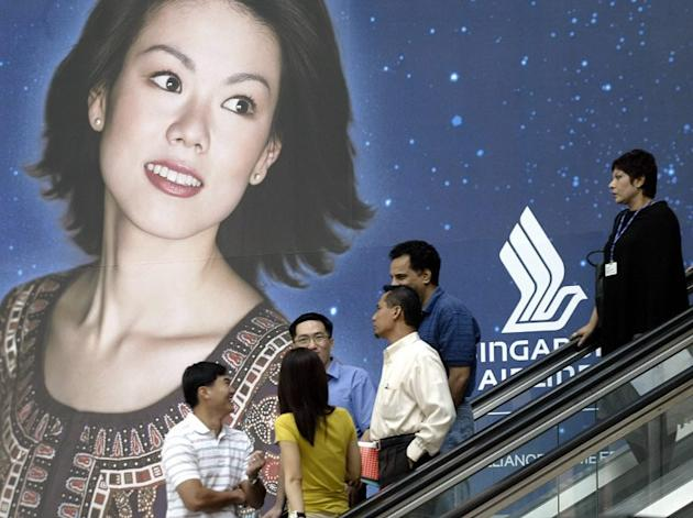 The SIA Girl, seen here in a giant poster at Raffles Place, is still seen as the epitome of poise and grace, but what's life really like for those flying the friendly skies? (AFP file photo)