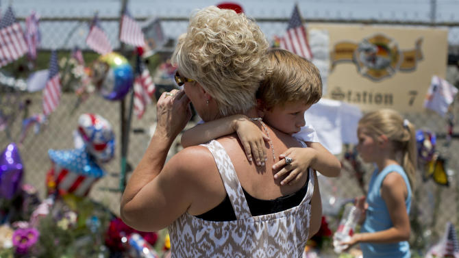 Lynn Paupore walks along the makeshift memorial with her grandson Bradley Richtig, 5, and granddaughter Kylie Richtig, 8, outside the Granite Mountain Interagency Hotshot Crew fire station, Wednesday, July 3, 2013 in Prescott, Ariz. A mile-high city about 90 miles northwest of Phoenix, Prescott remains a modern-day outpost of the pioneer spirit. It's that spirit that will guide officials as they navigate the days ahead and figure out how to honor the elite Hotshot firefighters who died Sunday in a nearby wind-driven wildfire that is still burning. (AP Photo/Julie Jacobson)