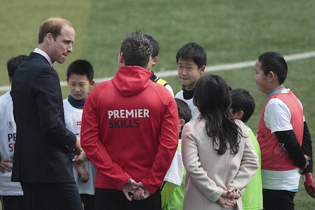 Britain's Prince William, left, meets with students as he attends the Premier Skills football coaching event at Nanyang Secondary School in Shanghai, China Tuesday, March 3, 2015. William focused