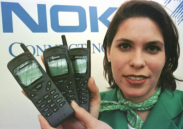 FILE - This is a Tuesday March 12, 1997 file photo of Tanja Stefezius as she holds Nokia 3110 cellular phones at the CeBIT'97 exhibition in Hannover Germany. Nokia, the once-mighty star of cellphone giant and source of national pride for Finland, has been brought low by the news Tuesday Sept. 3, 2013 that Microsoft Corp. was acquiring its cellphone operations. Once the bellwether of the wireless industry, Nokia Corp. led the innovative industry for more than a decade, reaching a peak of 40 percent market share in mobile phone sales worldwide in 2008 a long step for the former paper maker and producer of rubber boots, which was founded in 1865 and was based in and named after the small southern Finnish town of Nokia. (AP Photo/Fabian Bimmer, File)