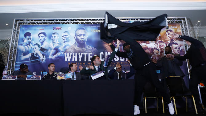 Dillian Whyte, trainer Mark Tibbs, Sky Sports' Adam Smith, promoter Eddie Hearn and promoter Kalle Sauerland look on as Dereck Chisora throws a table during the press conference