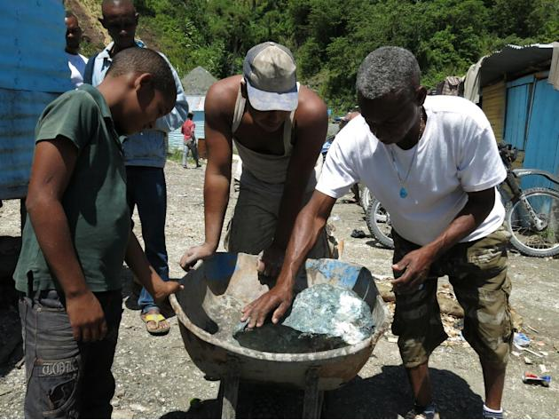In this March 18, 2015 photo, miners look at a recently extracted larimar stone in Las Filipinas, Barahona province, Dominican Republic. The local mining cooperatives have held the right to dig since