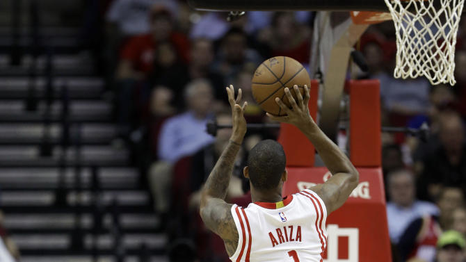 Houston Rockets' Trevor Ariza (1) charges into Sacramento Kings' DeMarcus Cousins (15) for an offensive foul in the first half of an NBA basketball game Wednesday, April 1, 2015, in Houston. (AP Photo/Pat Sullivan)