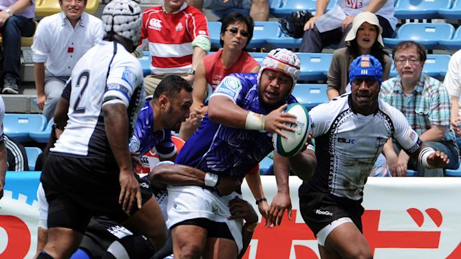Samoa's Ole Avei is tackled by a player