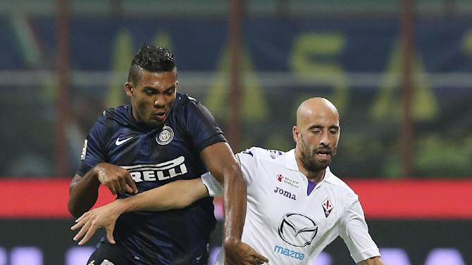 Inter Milan Brazilian defender Juan Jesus, left, challenges for the ball with Fiorentina midfielder Borja Valero during the Serie A soccer match between Inter Milan and Fiorentina at the San Siro stadium in Milan, Italy, Thursday, Sept. 26, 2013