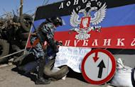 A pro-Russian armed man displays a banner at a check point outside the eastern Ukrainian city of Slavyansk, on April 26, 2014