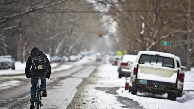 A man makes his way down Ivinson Street on his bicycle heading towards the University of Wyoming campus during a springtime snow storm that moved through Laramie, Wyo., Tuesday, April 9, 2013. (AP Photo/Laramie Boomerang, Jeremy Martin)