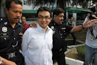 Abdul Razak Baginda (C), a high-profile political analyst, walks towards the court room in police custody in Shah Alam, west of Kuala Lumpur, in 2008. A scandal linking Malaysia's leader, a young woman's murder and alleged kickbacks in a French submarine deal has resurfaced as a potential danger for the government as elections loom