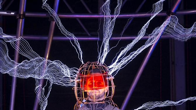 "Magician David Blaine stands inside an apparatus surrounded by a million volts of electric currents streamed by tesla coils during his 72-hour ""Electrified: 1 Million Volts Always On"" stunt on Pier 54, Friday, Oct. 5, 2012, in New York. The stunt, sponsored by Intel, is the latest of daredevil endeavors by the magician whose previous stunts included being encased in ice for over 60 hours in Times Square. (AP Photo/John Minchillo)"