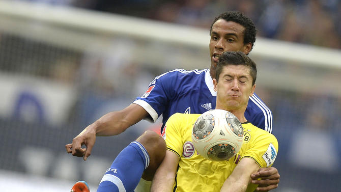 Dortmund's Robert Lewandowski, in front, and Schalke's Joel Matip challenge for the ball during the German Bundesliga soccer match between FC Schalke 04 and Borussia Dortmund in Gelsenkirchen, Germany, Saturday, Oct. 26, 2013