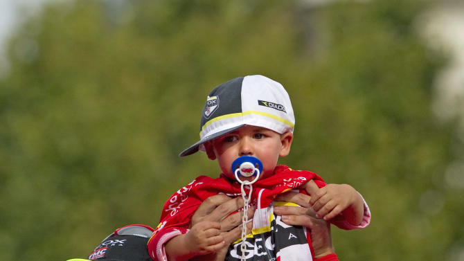 Geox-TMC team member Juan Cobo and his nephew Hugo, celebrate his victory on the podium in the Spanish Vuelta in Madrid, Spain, Sunday, Sept. 11, 2011. (AP Photo/Arturo Rodriguez)