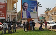 People stand under the poster of the Central African Republic's President Francois Bozize in Bangui on December 28, 2012. Government soldiers in the Central African Republic battled to re-capture a rebel-held city Friday, a military official said, despite regional efforts to seek a peaceful end to the growing crisis