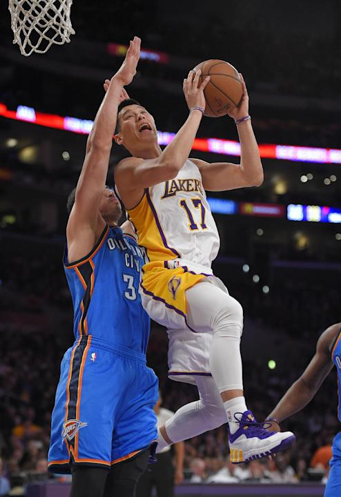 Los Angeles Lakers guard Jeremy Lin, right, shoots as Oklahoma City Thunder center Enes Kanter, of Turkey, defends during the first half of an NBA basketball game, Sunday, March 1, 2015, in Los Angele