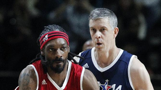 U.S. Education Secretary Arne Duncan, of the East team, follows West's Snoop Dogg, aka Snoop Lion, during the second half of the NBA All-Star Celebrity basketball game in New Orleans, Friday, Feb. 14, 2014. The East won 60-56