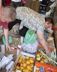 "People fill up bags with fruits and vegetables for distribution to needy people in a working class neighbourhood of Madrid, on June 1. The ""indignants"" are currently building an extraordinary street-level network to help those hardest hit by economic hardship"