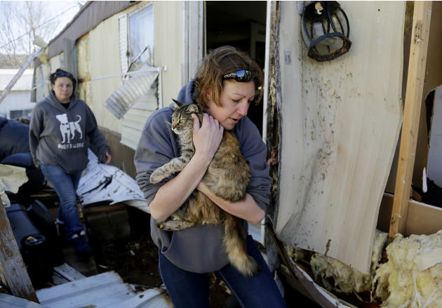 Marci Euliss carries a cat from a badly damaged mobile home as Misty Bilby follows at River Oaks mobile home community, Thursday, March 26, 2015, a day after the first batch of severe weather in this