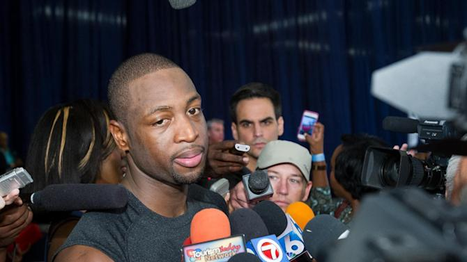 Miami Heat point guard Dwayne Wade speaks to reporters during a break from a training camp session at the Atlantis Resort in Paradise Island, Bahamas, Tuesday, Oct. 1, 2013. The two-time defending NBA champions opened training camp Tuesday at the resort, with two practices scheduled for opening day