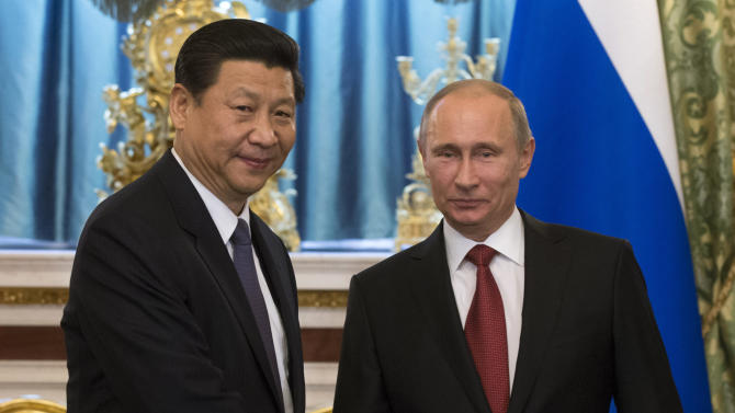 Russian President Vladimir Putin, right, and Chinese President Xi Jinping shake hands during their meeting in the Kremlin in Moscow, Russia, Friday, March 22, 2013. Russia is Xi Jinping's first foreign destination as China's president. Xi's talks with Putin on Friday are set to focus on oil and gas as China seeks to secure new energy resources to fuel its growing economy. (AP Photo/Alexander Zemlianichenko, Pool)