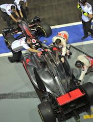 McLaren-Mercedes' British driver Jenson Button's formula one race car rolls in for a pit stop during the second practice session of Singapore's Formula One