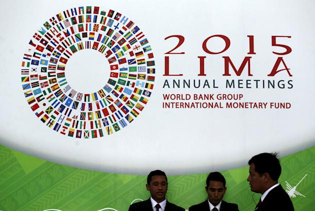 People stand near a welcome sign to the 2015 IMF/World Bank annual meetings at the venue of the event in Lima