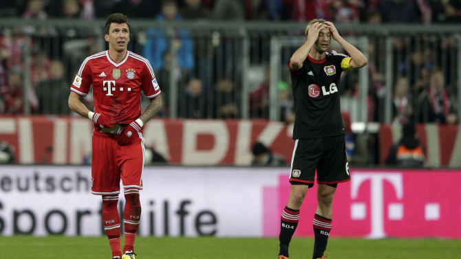 Bayern's Mario Mandzukic of Croatia, left, watches the stadium board after scoring his side's opening goal as Leverkusen's Simon Rolfes gestures during the German first division Bundesliga soccer match between FC Bayern Munich and Bayer 04 Leverkusen, in Munich, southern Germany, Saturday, March 15, 2014