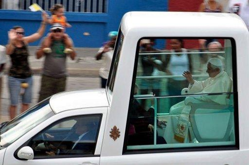 Pope Benedict XVI waves to Cubans as he leaves in his Popemobile
