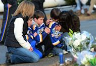 Children and their parents pay tribute to the victims of an elementary school shooting in Newtown, Connecticut, on December 15, 2012. Shattered families and grieving residents struggle to grasp the news that most of the 27 people shot dead by a gunman were children aged just six and seven