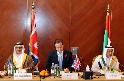 A handout picture released by the office of Dubai ruler Sheikh Mohammed bin Rashed al-Maktoum shows British Prime Minister David Cameron (C) sitting between Emirati Minister of State for Foreign Affairs Anwar Mohammed Gargash (L) and Emirati Economy Minister Sheikh Sultan bin Said al-Mansuri during a meeting in the Gulf emirate of Dubai