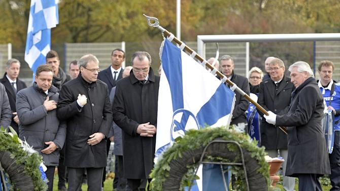 Schalke legend striker Klaus Fischer, supervisory board  chairman  Clemens Toennies, board member Peter Peters and sporting manager Horst Heldt, from right, stand at the grave of Adolf Urban, a storied player for soccer club FC Schalke 04 who was killed in Eastern Front fighting in World War II, being reburied in a cemetery in Gelsenkirchen, Germany, Wednesday, Nov. 20, 2013. Urban helped Schalke win five German championships and one German cup before he died 1943 in Russia. His body returned home after 70 years now to a cemetery overlooking the Schalke stadium