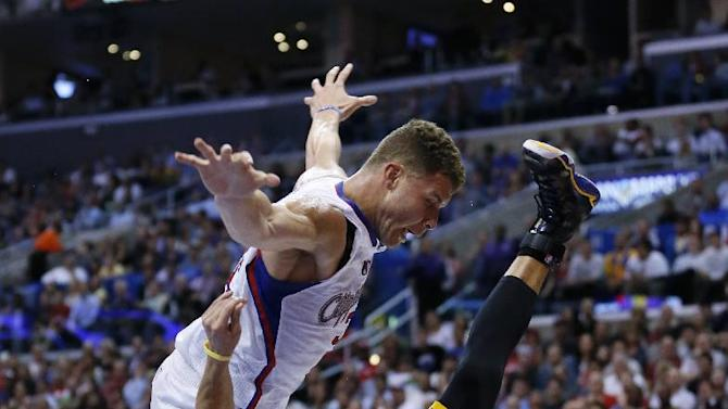 Los Angeles Clippers' Blake Griffin, left, collides with and is fouled by Golden State Warriors Stephen Curry, right, as Griffin went to the basket during the second half of an NBA basketball game in Los Angeles, Wednesday, March 12, 2014