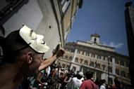 A demonstrator protests outside the Italian parliament in Rome on July 11. Market jitters over Italy eased on Friday after a successful bond auction despite a ratings downgrade by Moody's, which warned that short-term economic prospects were worse and political risk had increased