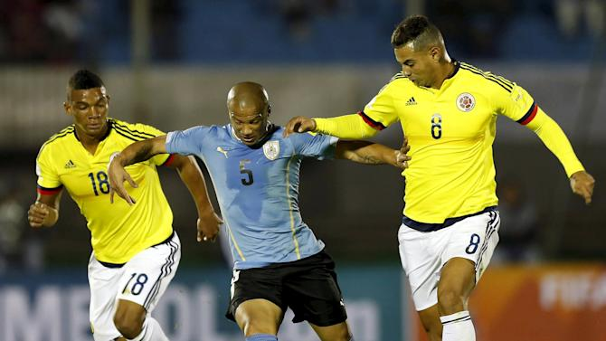 Uruguay's Carlos Sanchez fights for the ball with Colombia's Edwin Cardona and Frank Fabra during their 2018 World Cup qualifying soccer match at the Centenario stadium in Montevideo